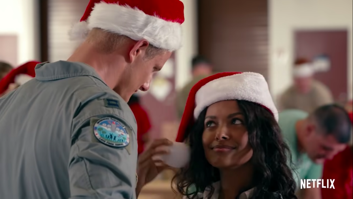A woman in a Santa hat looks up at a tall blonde man in the same hat.