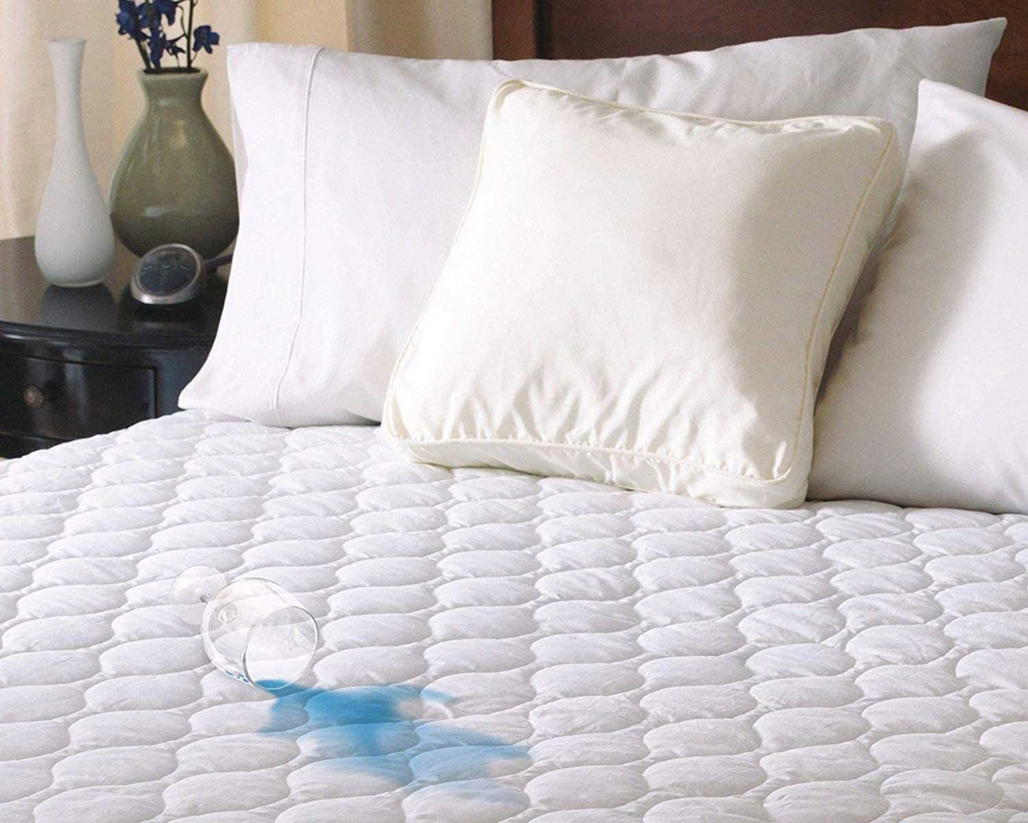 A Sunbeam water-resistant mattress pad on a bed with a spilled glass of water beading up on it.