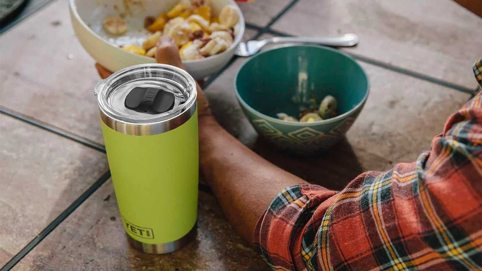 A YETI tumbler, sitting on a tile counter next to a man eating lunch.