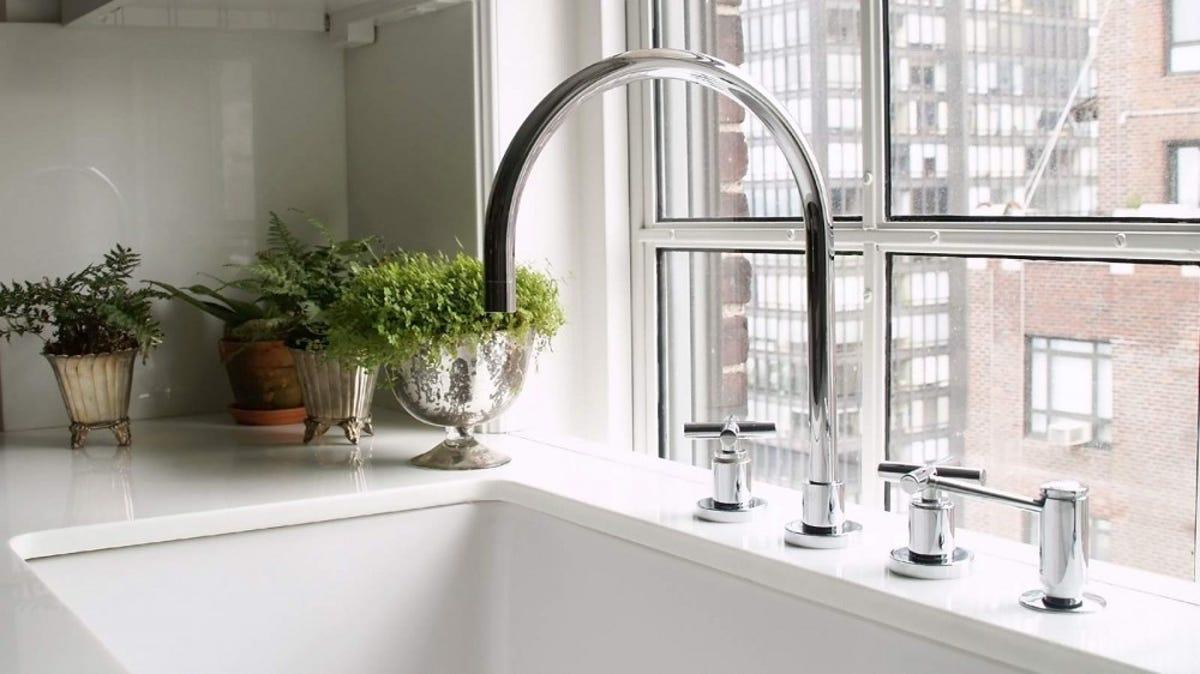 A kitchen sink overlooks a city.