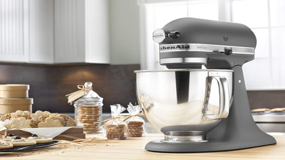 A KitchenAid mixer with freshly baked cookies in the background.