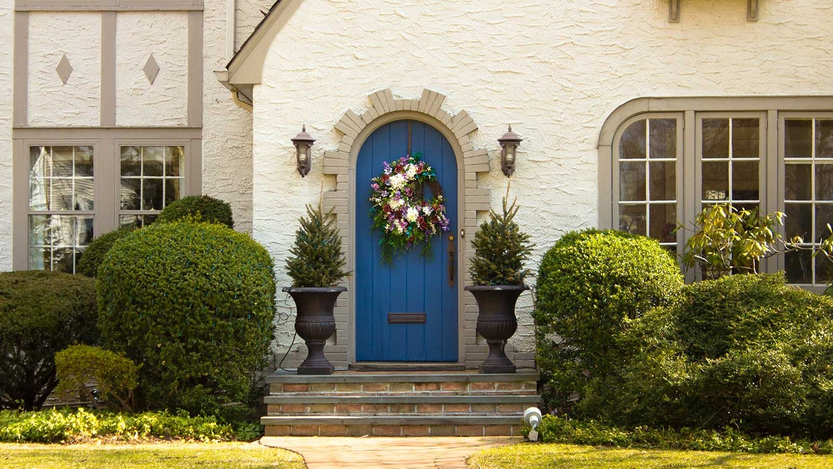 A colorful blue door on a traditional home with well done landscaping.