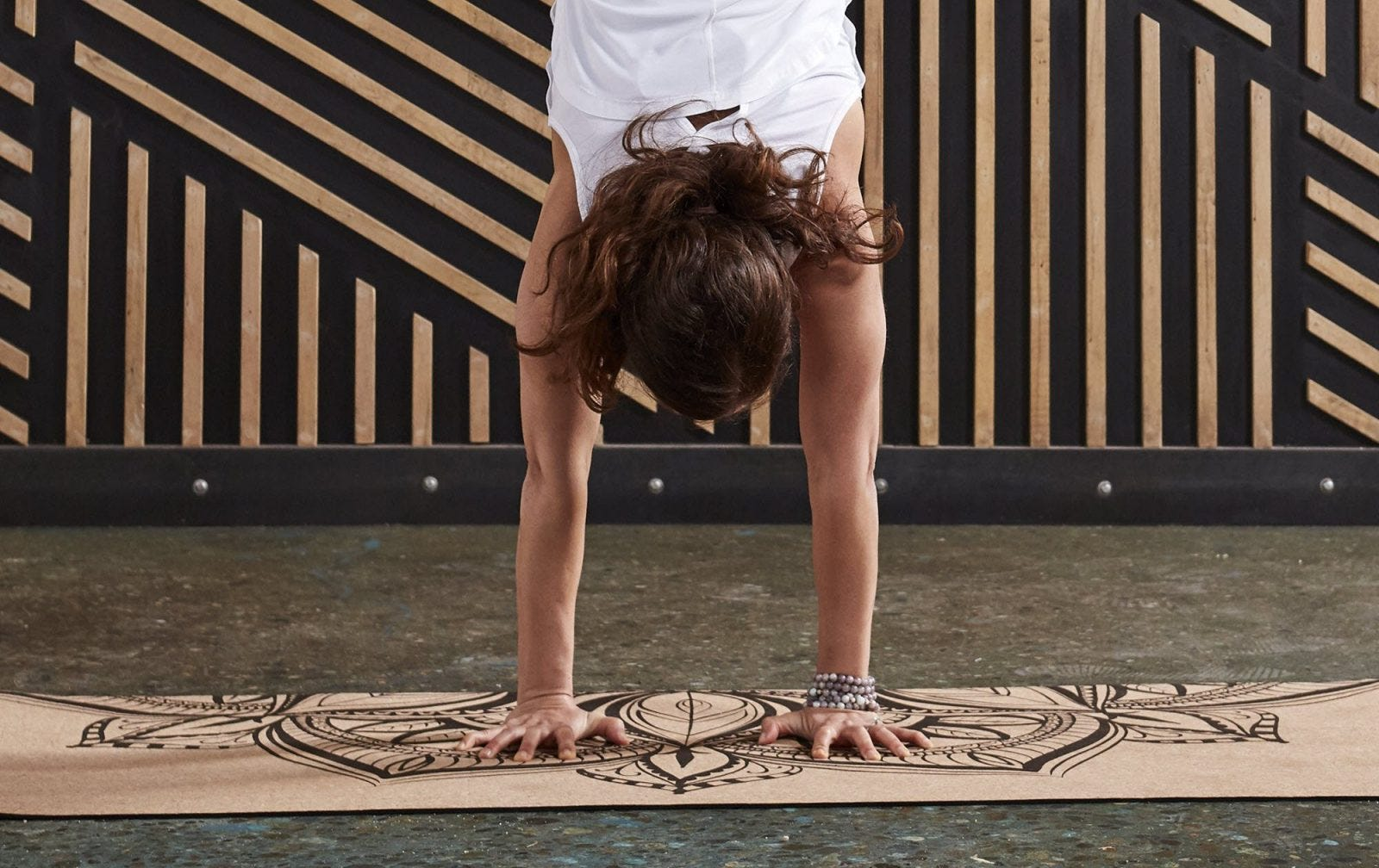 A woman in a yoga pose on a Gaiam cork yoga mat.