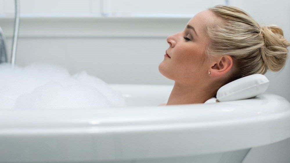 Woman relaxing in the tub with a bath pillow.