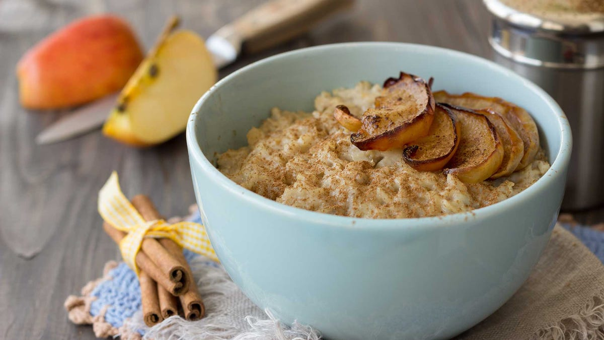 Oatmeal with baked apples and cinnamon in blue ceramic bowl on wooden table.