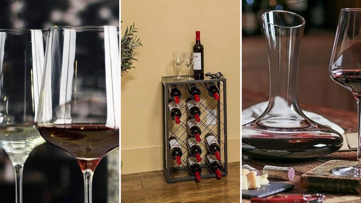 Two tulip wine glasses, a wine rack/side table, and red wine in a glass decanter.