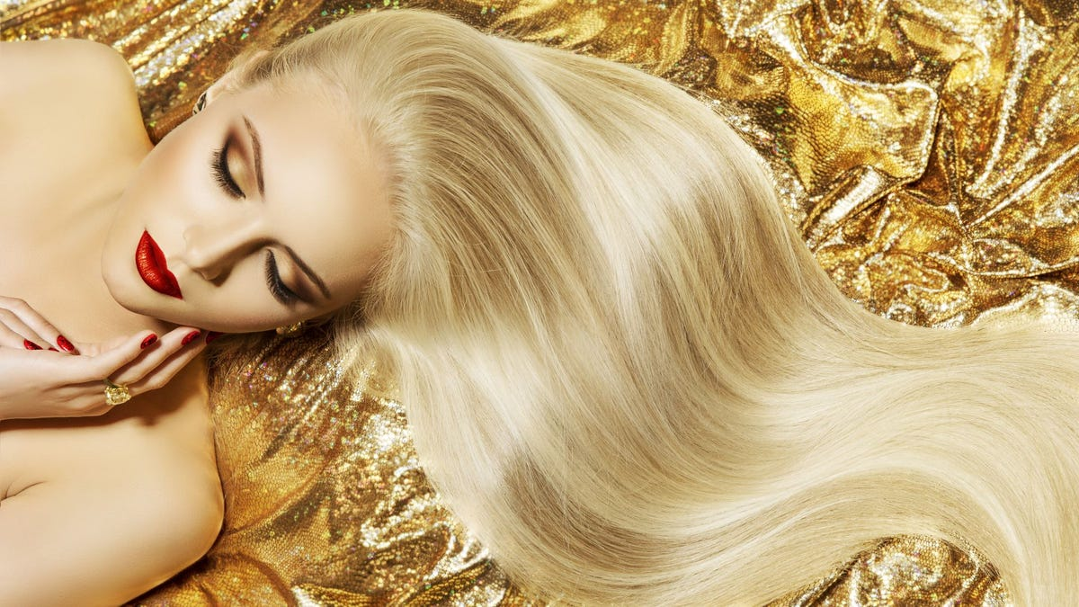 A woman with long blonde hair lying on a gold blanket.