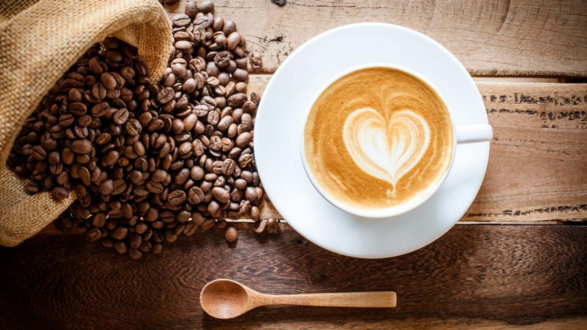 A bag of coffee beans is spilled onto a wooden table and surround a cup of coffee.