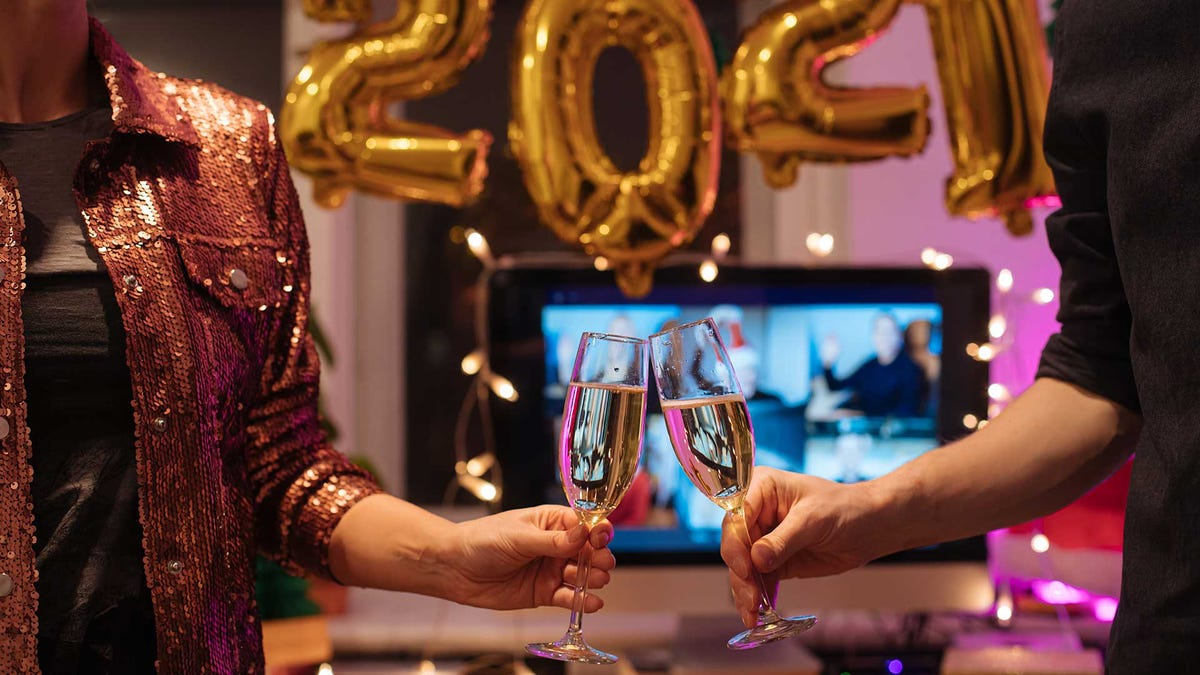 Couple toasting with champagne, celebrating New Year's Eve 2020 at home.