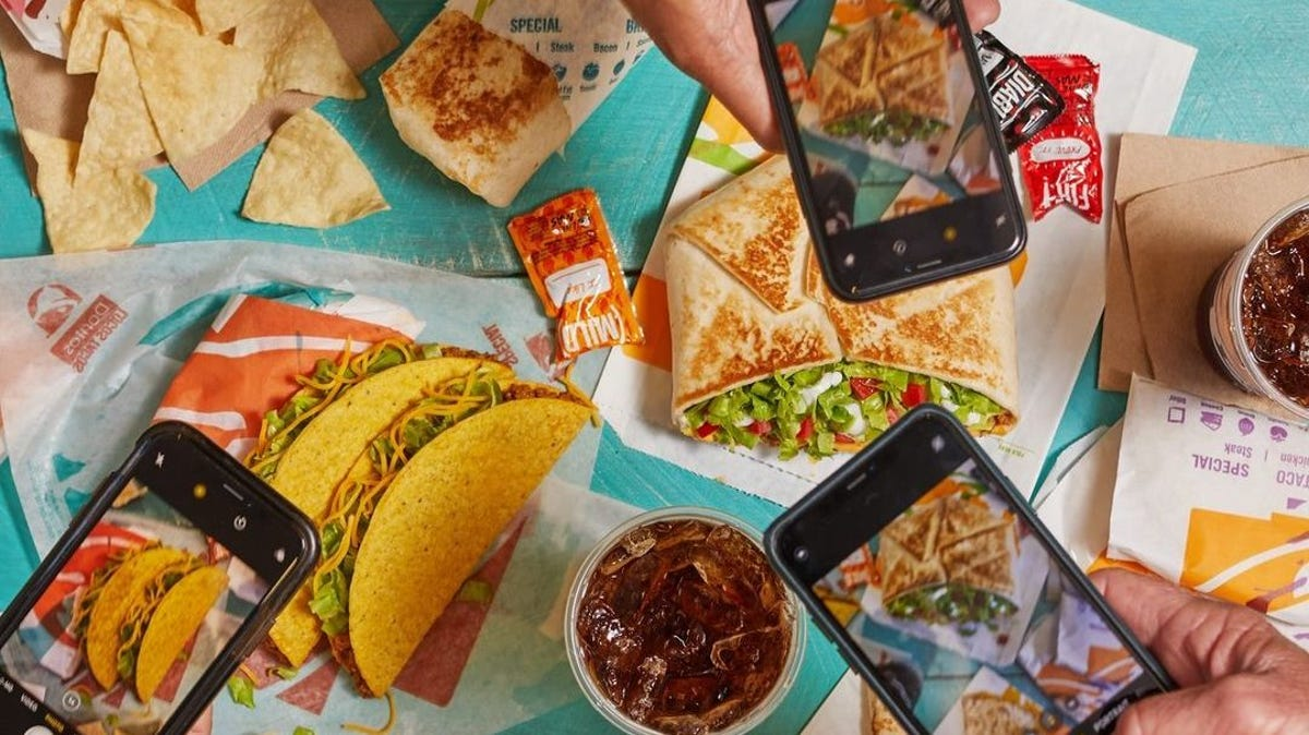 A buffet of Taco Bell foods is scattered over a table as people take photos.