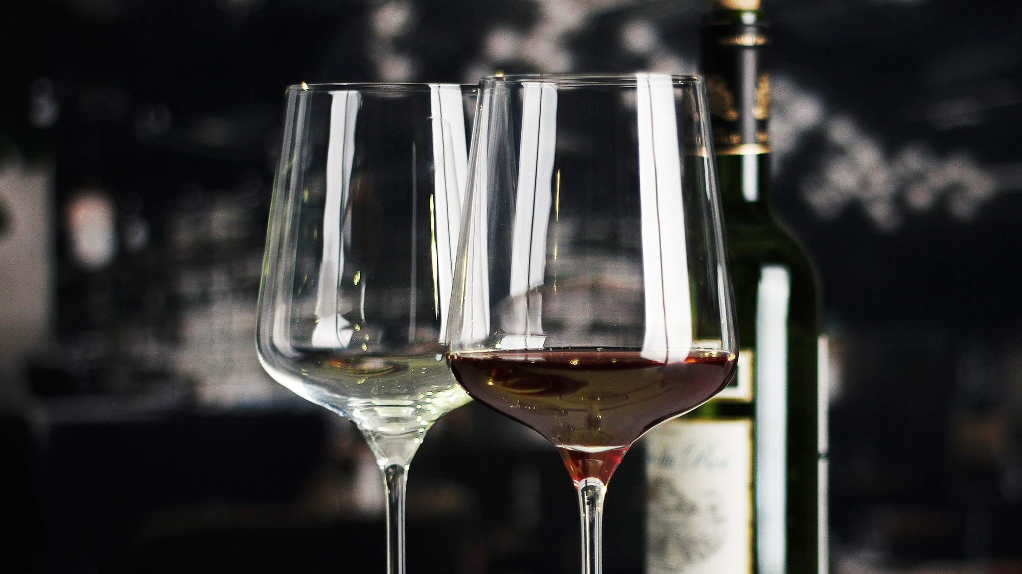 Two wine glasses, one with red wine and one with white, in front of a corked bottle.