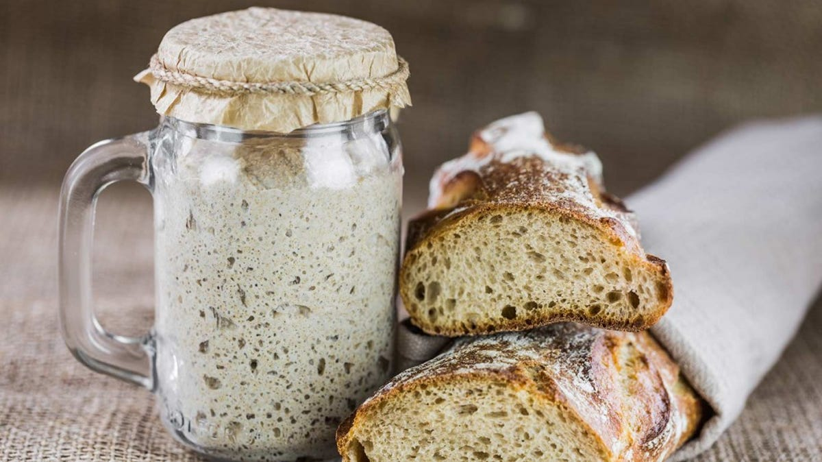 A loaf of sourdough sits next to a jar of starter.