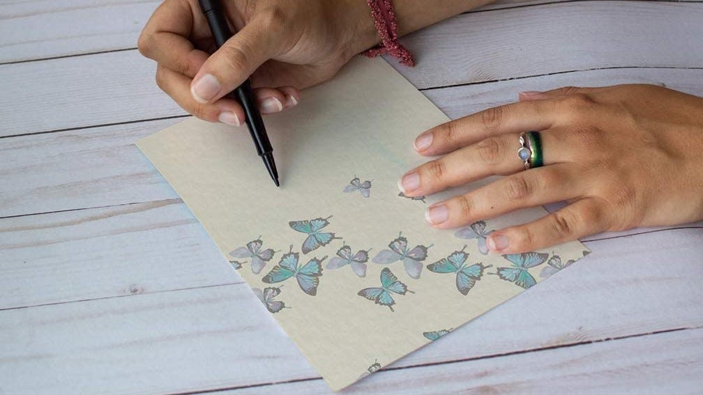 A person writing a note on a tree-free card.
