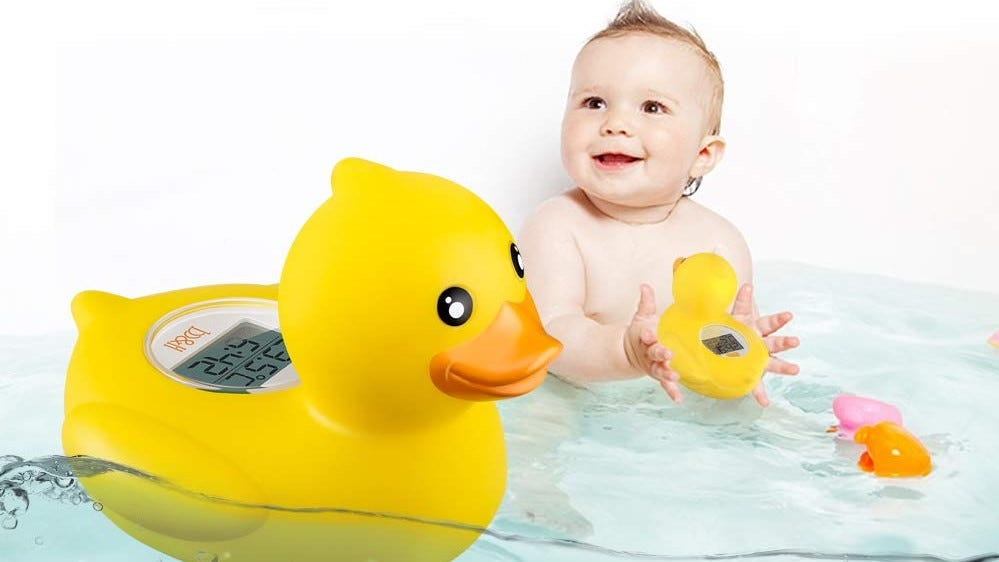 A baby in a tub with the rubber duckie thermometer.