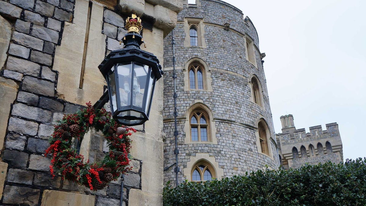 A picture of Windsor Castle with holiday wreathes hung on the lanterns.