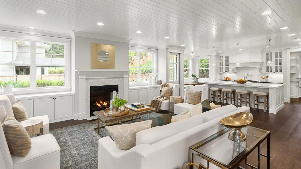 Sunlight fills a white, open-concept living room.