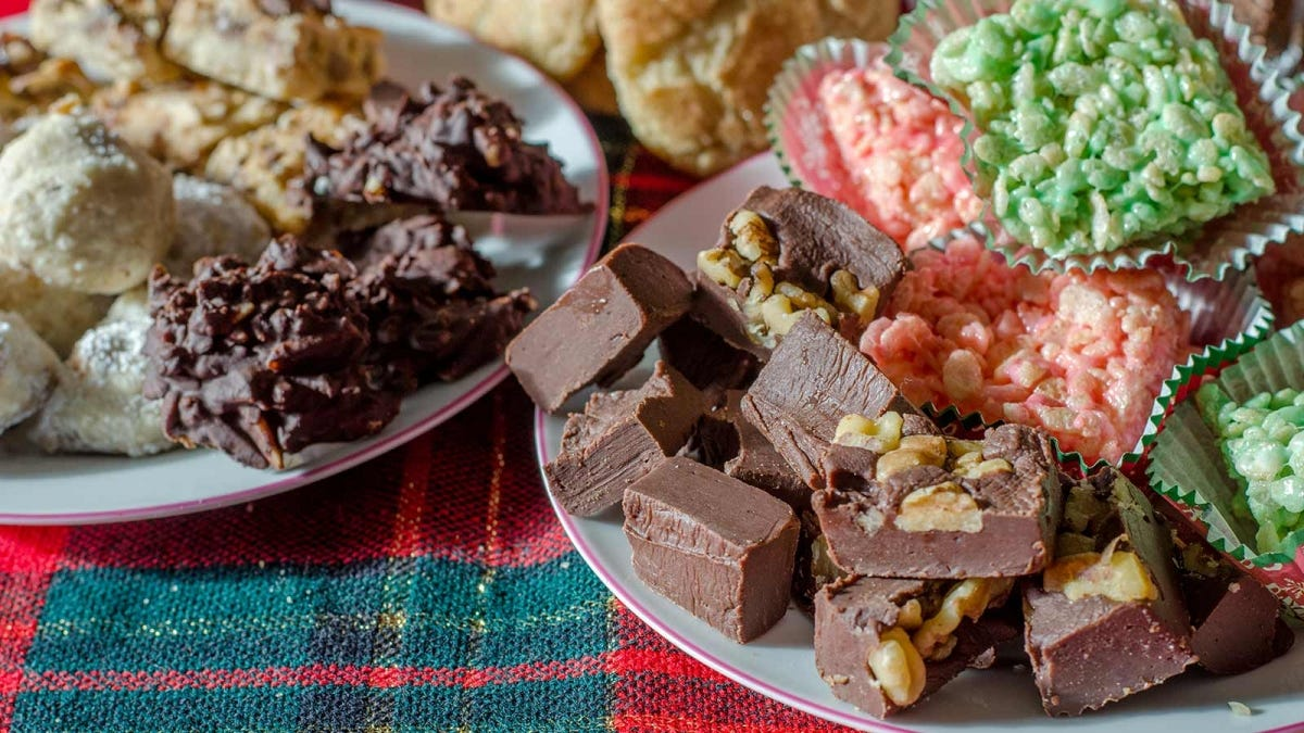 A table holds several plates filled with various Christmas desserts.