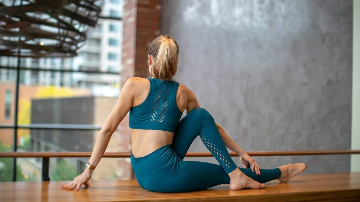 A woman doing a yoga twist in a dark green athletic set.