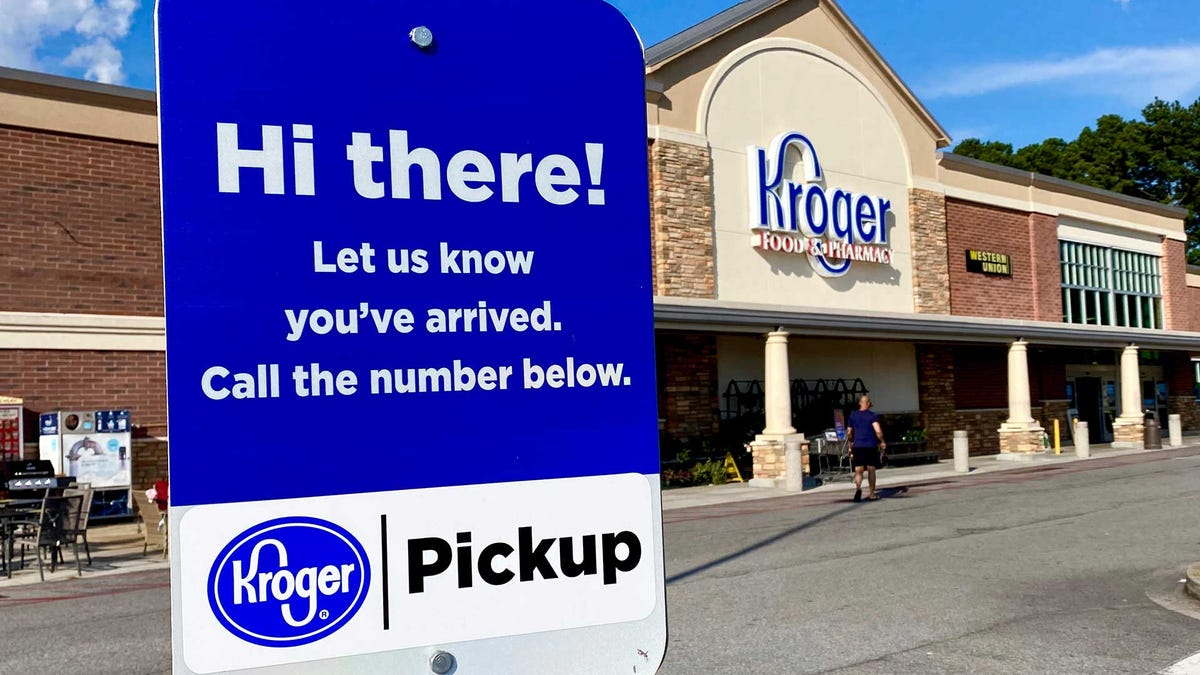 An exterior of a Kroger grocery store with a grocery pickup location sign visible.