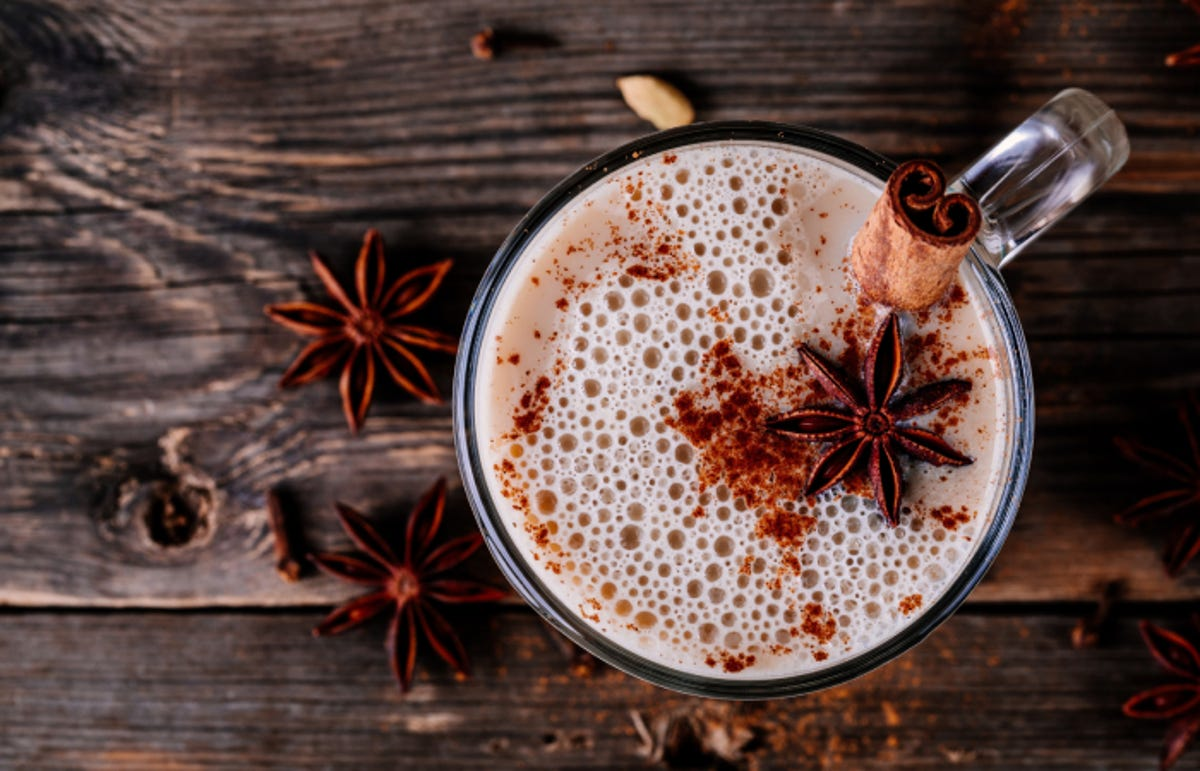 top view of a homemade chai tea latte with anise and cinnamon stick in glass mug on wooden rustic background