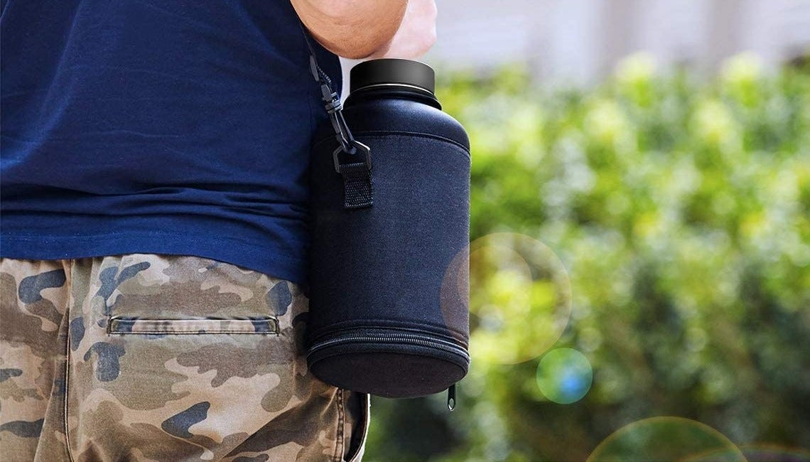 A man carrying water in an insulated canteen bottle while walking.