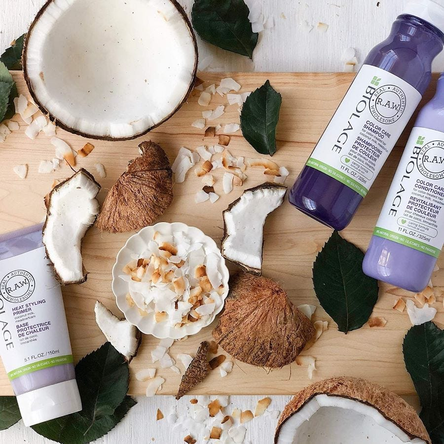 Two bottles and one tube of Biolage R.A.W. Color Care Shampoo surrounded by coconuts.