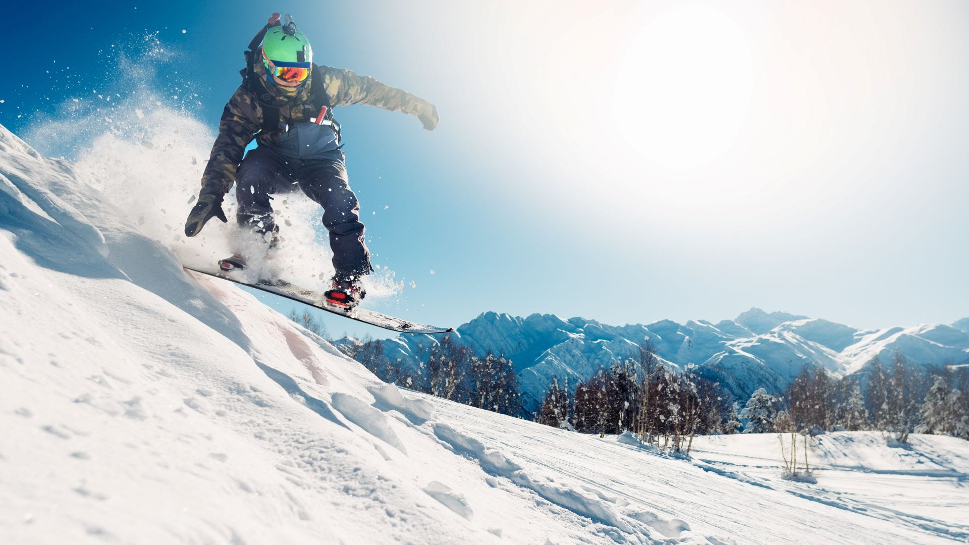 A snowboarder coming down a snow-covered hillside.