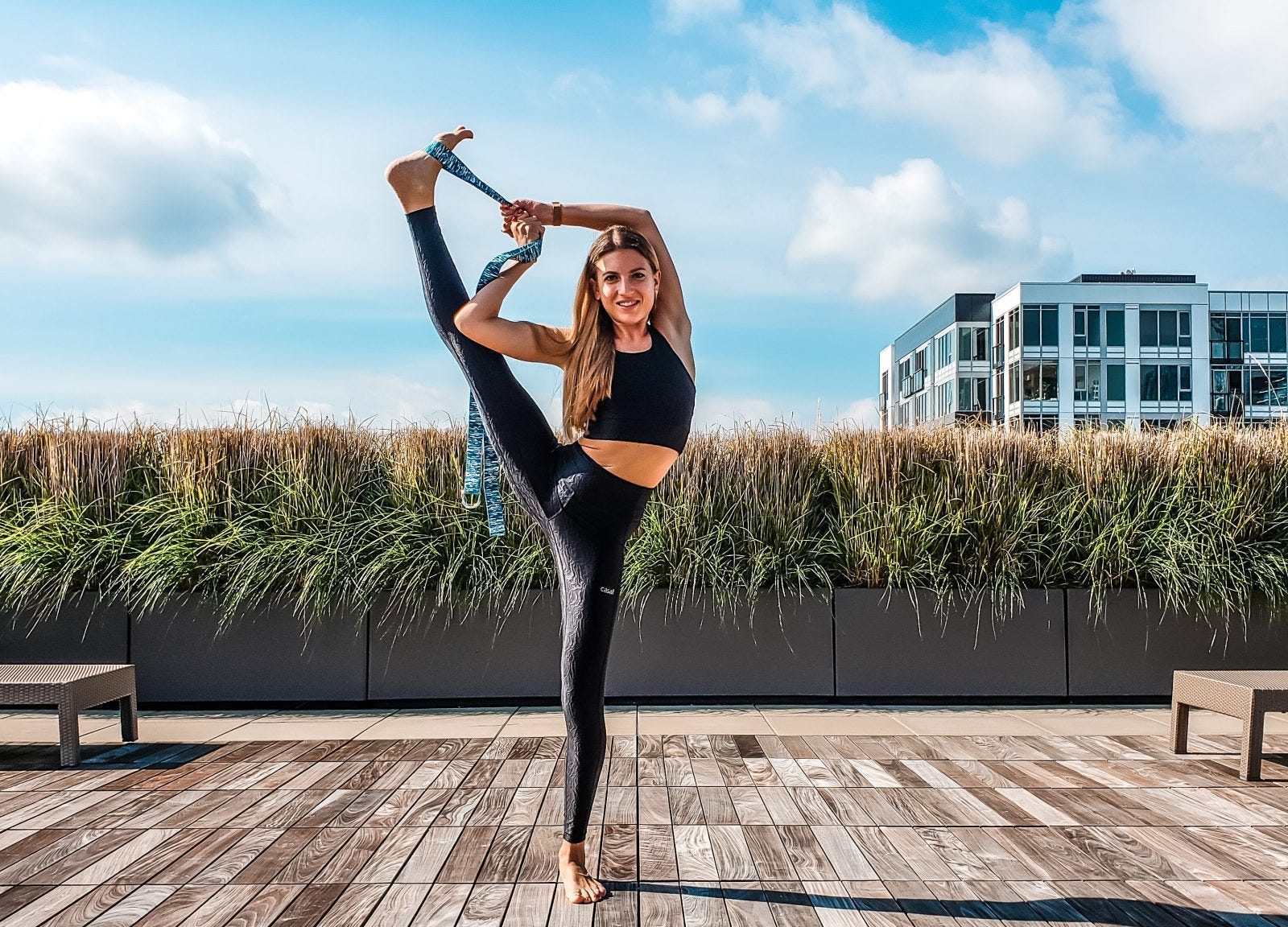 A woman using a yoga strap to do a leg stretch on a rooftop.