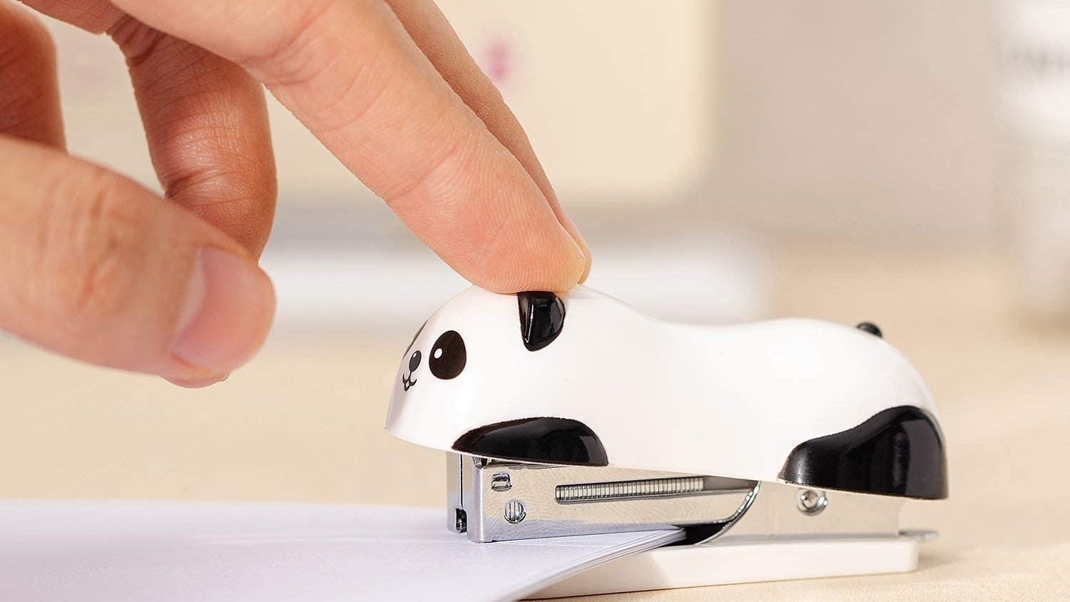 Panda stapler being used to staple papers.