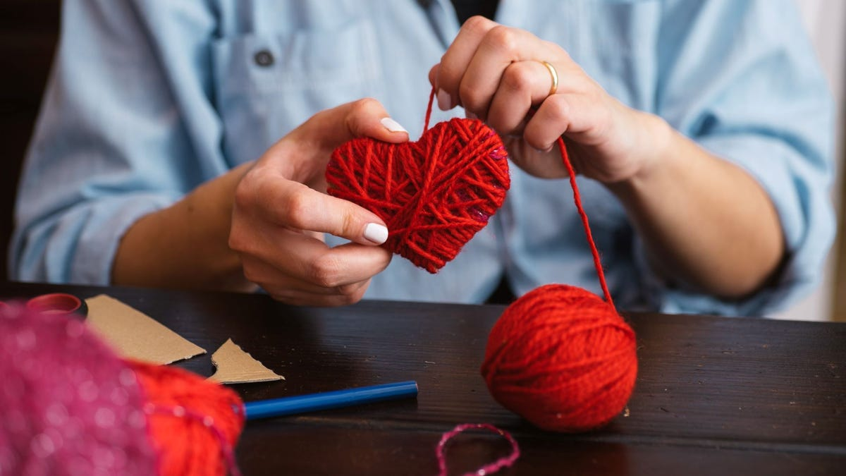 Someone making a heart out of red yarn at a craft table.