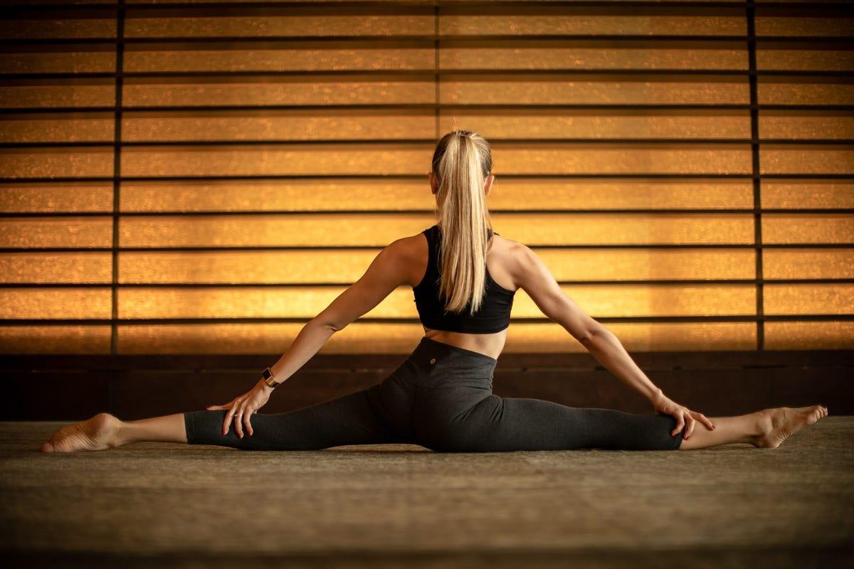 A woman doing a yoga split.