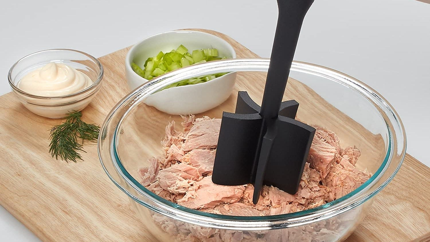 Meat masher being used on a bowl of chicken.