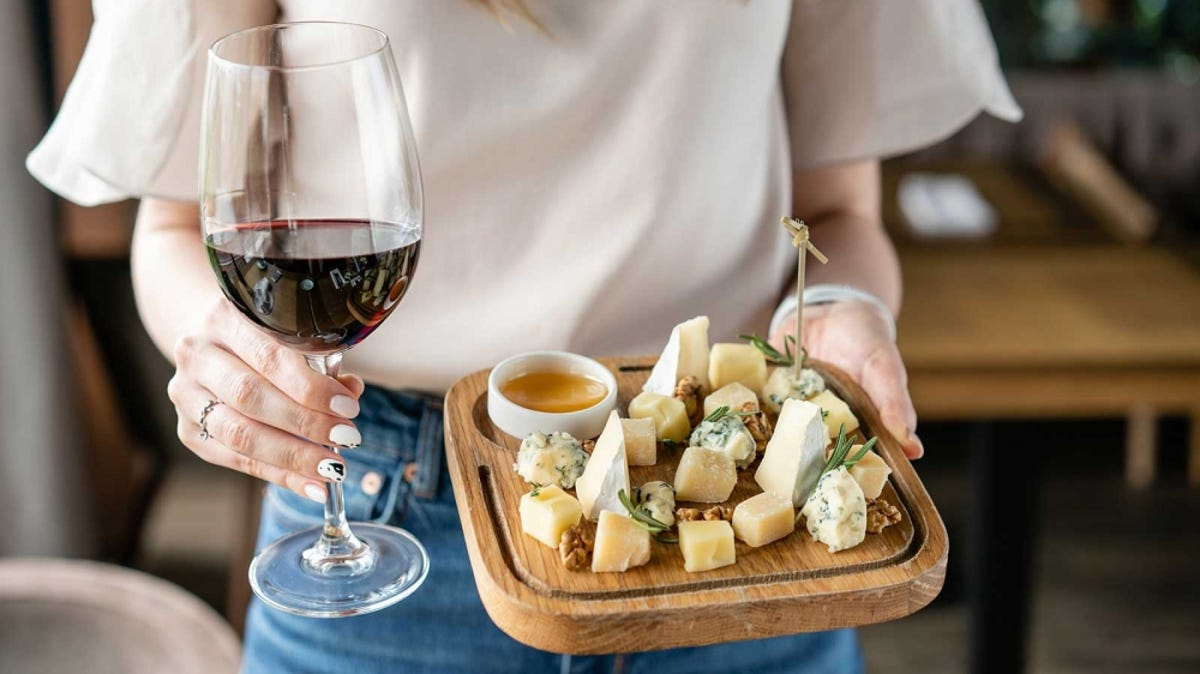 A woman holds a small cheese plate and a glass of wine.