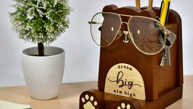 Bear pen holder on a desk, holding eye glasses.