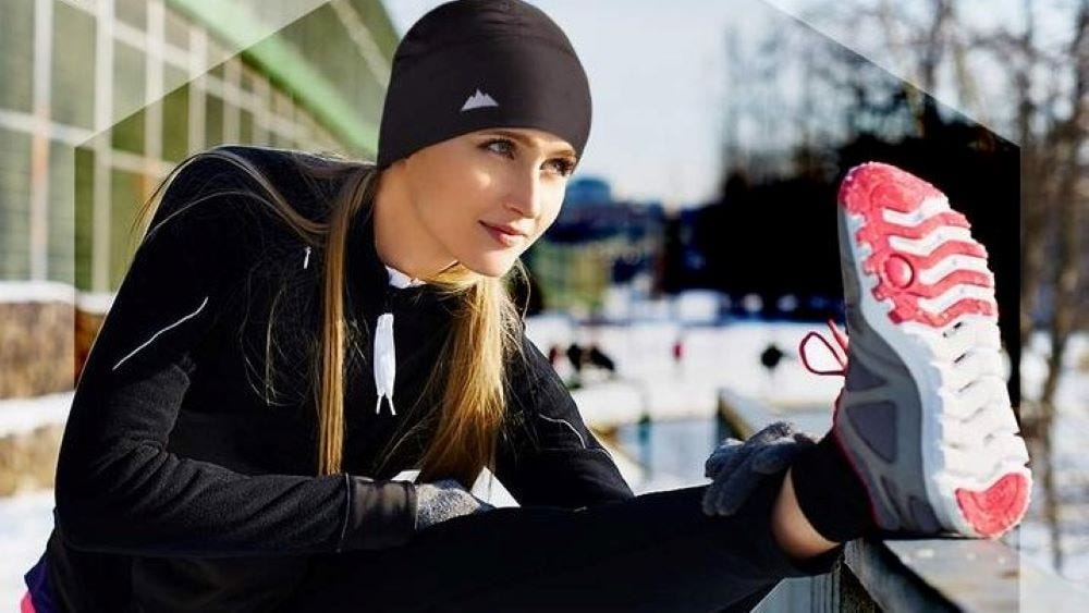 A woman stretching outside wearing a black Skull Cap.