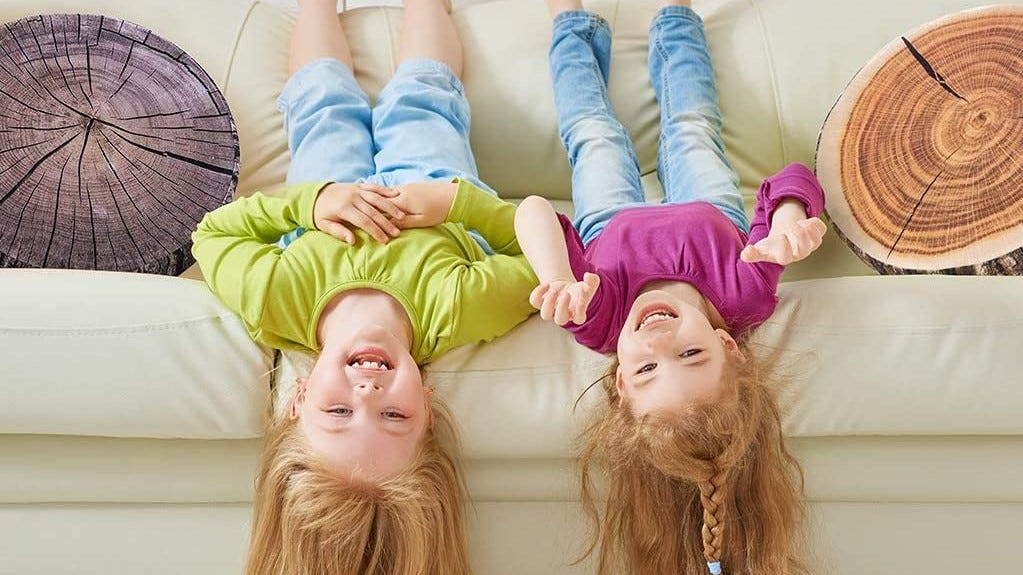 Two little kids playing on a couch next to two different wood slice pillows.