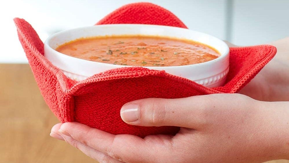Person holding a bowl of soup in s fabric soup holder.