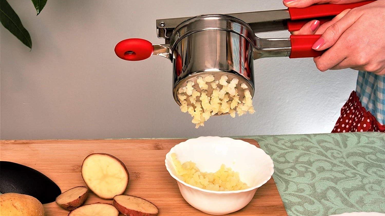 A person using a potato ricer to mash potatoes.