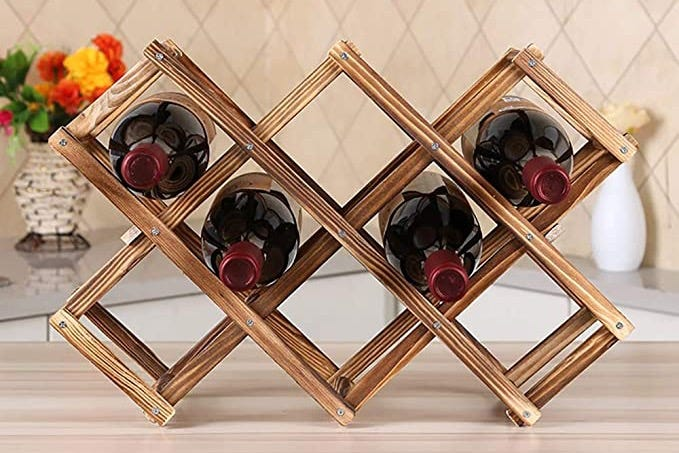 Four bottles of wine in a small countertop wine rack.