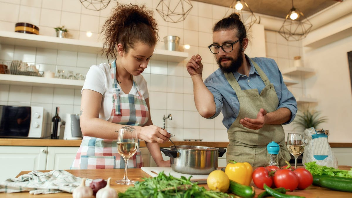 A woman and man prepping a dish in a sauce pan on a kitchen counter.