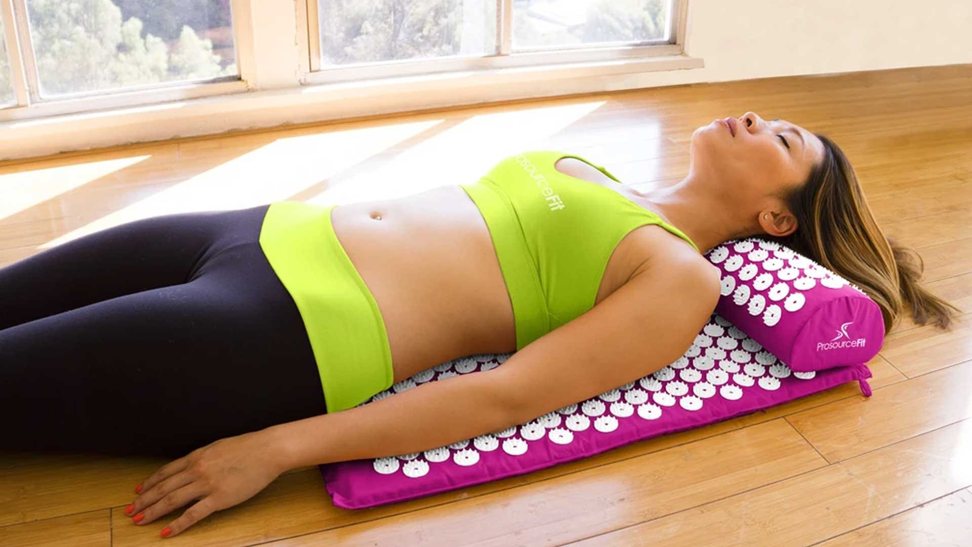 A woman laying on a pink acupressure point mat.