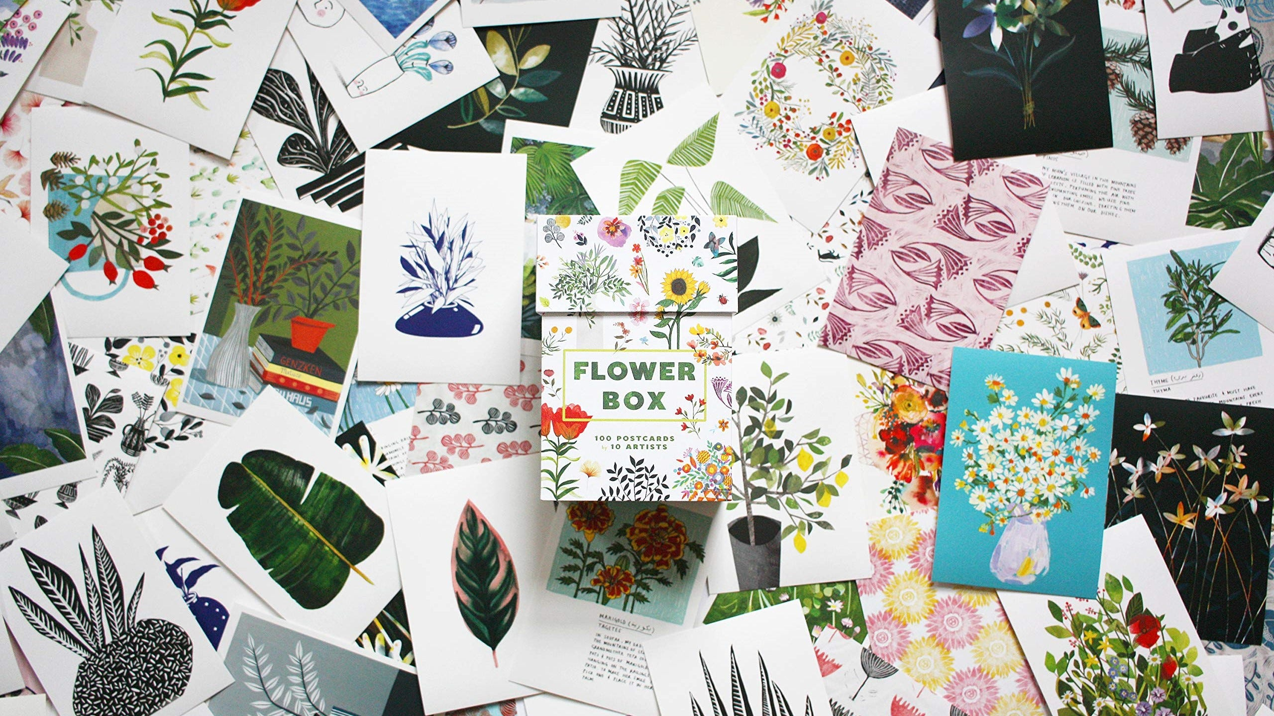 Botanical postcards stacked around the box they come in.
