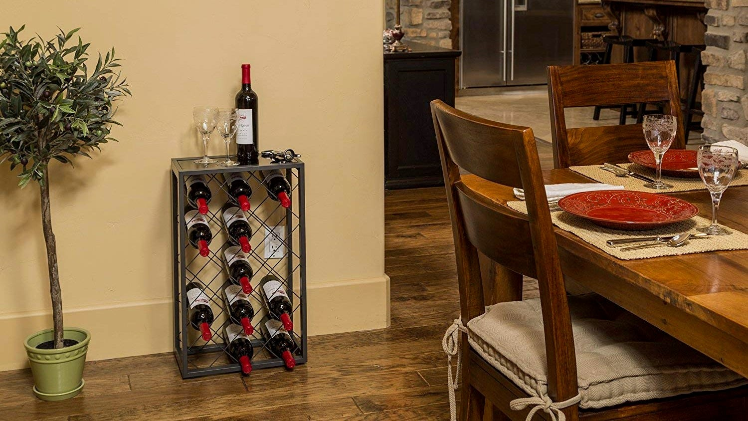 A freestanding wine rack against a wall in a dining room, next to a houseplant.