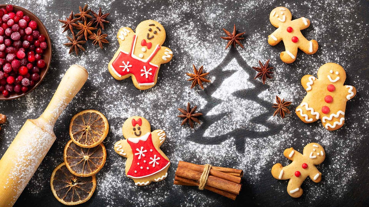A kitchen counter with a rolling pin, Christmas cookies, powdered sugar, and other ingredients.