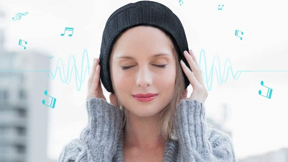 A woman listening to music with her Bluetooth speaker hat.