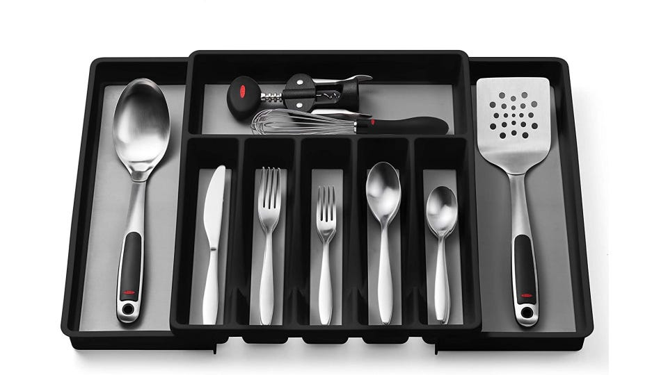 Gray and black cutlery organizer filled with kitchen utensils.