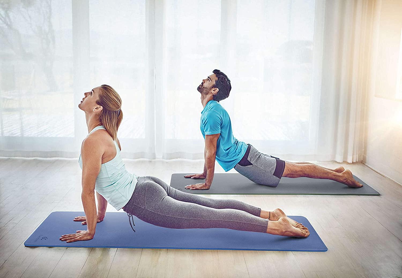 A man and woman doing the yoga cobra pose on Ewedoos yoga mats.