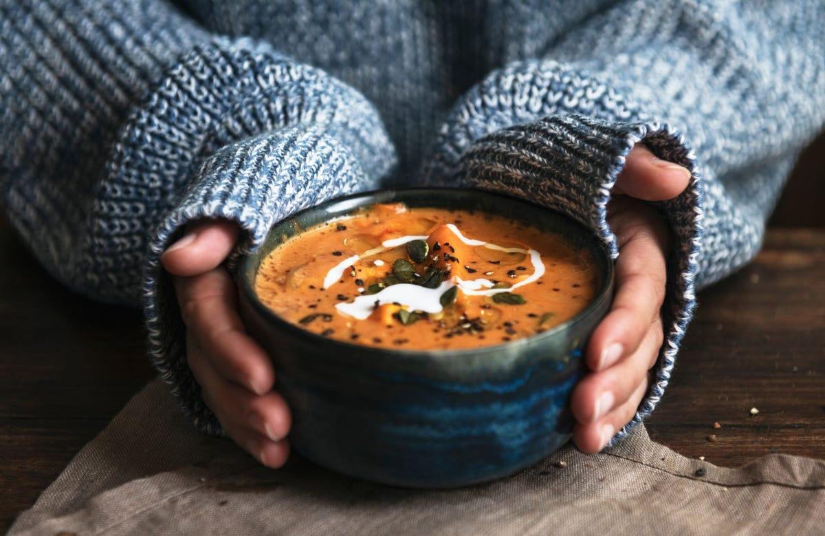 A woman holding a bowl of tomato soup.