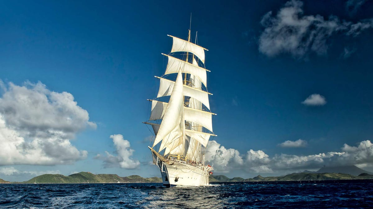 A sailing ship with brilliant white sails framed against a a tropical island and blue skies.