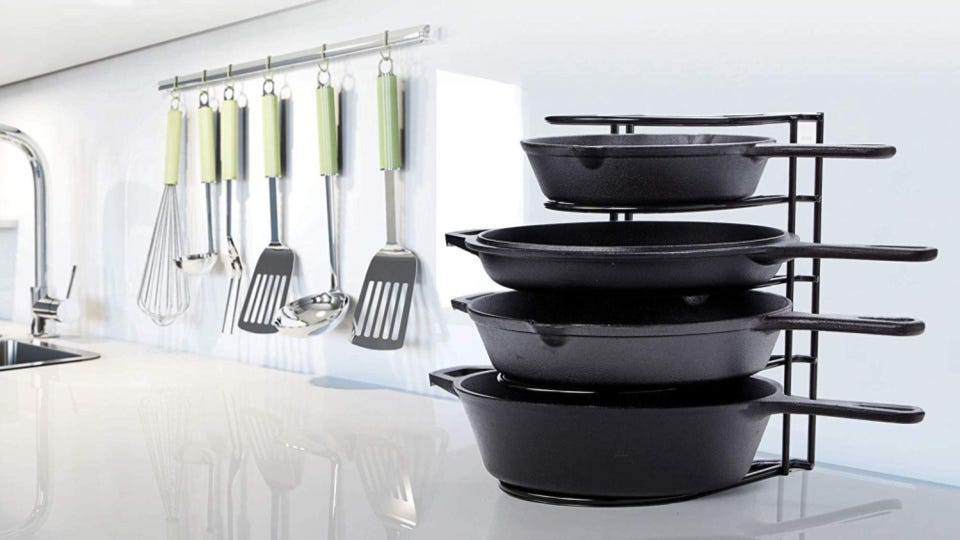 A Cuisinel rack holding four cast-iron skillets.